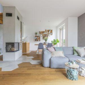 Nowoczesny modny salon w domu jednorodzinnym. Drewno na podłodze i pięknych schodach zestawione z bielą i szarościami. Projekt: Zuzanna Kuc, Zu Projektuje. Fot. Pion Poziom