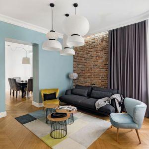 Czerwona cegła na ścianie za kanapą w salonie pięknie koresponduje z błękitem. Projekt Anna Maria Sokołowska. Fot. Paweł Mądry