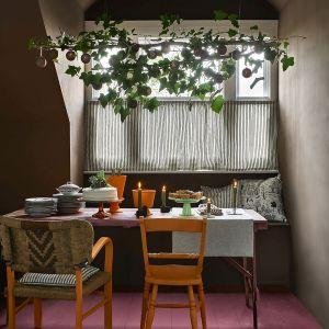 Ściany wykończone Chalk Paint™ w kolorze Honfleur, stół w kolorze Burgundy, krzesła i ceramiczne wazony w kolorze Barcelona Orange, bombki pomalowane Chalk Paint™ w kolorach Burgundy, Honfleur, Amsterdam Green  i ozdobione woskiem pozłotniczym Gilding Wax. Fot. Annie Sloan