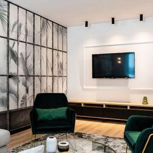 Butelkowa zieleń w salonie - w tym wnętrzu w postaci zielonych mebli tapicerowanych i pięknej botanicznej tapety na ścianie. Projekt: DG Studio Donata Gadalska. Fot. Jacek Fabiszewski