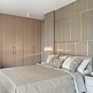Tapicerowane łóżko w sypialni, ściana za łóżkiem to modułowa ściana z tapicerowanych paneli. Projekt: Katarzyna Kraszewska. Fot. Tom Kurek