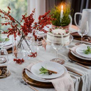 Świąteczna dekoracja stołu. W aranżacji: stół rozkładany Creative (blat nude, nogi proste dębowe), krzesło i taboret Simple (dębowe), osłonka na doniczkę średnia Redo, taca mała Ovo, talerz dekoracyjny Omni, podkładki Infra, serwetnik Serw Koral, talerze i dzban Pulve, patera Piato, kieliszek do wina białego Rubin, łyżki Ato, naczynia dekoracyjne Saga, pojemnik mały Jar, zawieszka mała Buli, taca mała Redo. Fot. VOX
