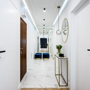 Aranżacja korytarza. Jasna kolorystyka i lustro powiększają przedpokój optycznie. Projekt i zdjęcia: Moovin Interiors