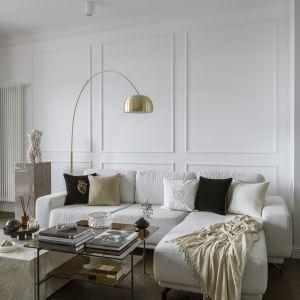 W salonie nie sposób nie zwrócić też uwagi na oświetlenie – złote lampy doskonale wpisują się w styl wnętrza. Projekt Kate&Co. Mieszkanie Koneser . Fot.YassenHristov