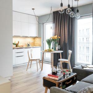 Okrągły stół z dwom krzesłami ustawiony został pomiędzy małym salonem a kuchnią. To bardzo wygodne rozwiązanie w otwartej, jasnej strefie dziennej. Projekt i zdjęcia: pracownia KODO Projekty i Realizacje Wnętrz