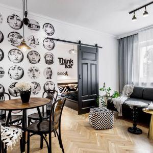 Jadalnia znajduje się w małym salonie. Obie strefy urządzono w duecie bieli i czerni z dodatkiem drewna. Projekt: Marta Piórkowska-Paluch. Fot. Andrzej Czechowicz, Foto Studio Wrzosy