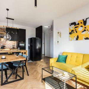 Jadalnia znajduje się w małym salonie i tuż przy kuchennej wyspie. Niebieskie krzesła świetnie pasują do żółtek kanapy. Jest ładnie i kolorowo. Projekt Deer Design. Fot. Fotomohito