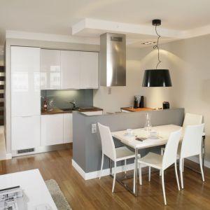 Miejsce na jadalnią wydzielono przy półwyspie kuchennym. Biały, plastikowy stół i krzesła pasują do małego salonu. Projekt: Lucyna Stanek Fot. Bartosz Jarosz