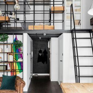 Metalowe półki tworzą spójną całość ze schodami prowadzącymi na antresolę. Projekt: Magdalena Załoga. Fot. Ayuko Studio