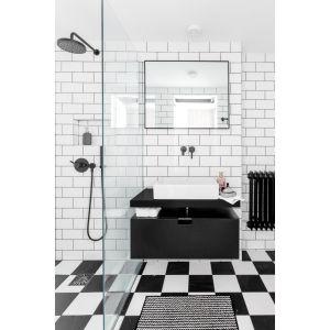 Białe kafelki, motyw szachownicy na podłodze oraz wyraziste, czarne dodatki w postaci szafki pod umywalkę, armatury i grzejnika tworzą spójną koncepcję, harmonizującą z industrialnym stylem mieszkania. Projekt: Magdalena Załoga. Fot. Ayuko Studio