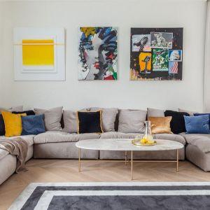 Ściana za kanapą w salonie pomalowana farbą, z kolorowymi obrazami. Projekt: Piotr Płużek, Piotr Płużek Studio. Fot. Marta Behling/Pion Poziom