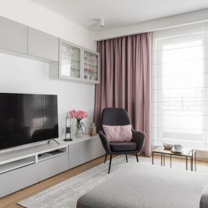 W jasnym salonie piękne wyglądają różowe zasłony. Są one w tym samym kolorze, co kolor poduszek. Aranżację okna uzupełnią białe rolety. Projekt: Barbara Wojsz. Fot. Fotomohito