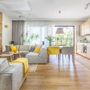 W jasnym, przytulnym salonie zastosowano dużo drewna. Całą aranżacje świetnie ożywiają dodatki w żółty kolorze. Projekt: Dorota Kudła. Fot. Pion Poziom