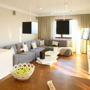 W jasnym, przytulnym salonie zdecydowano się na białe i  kremowe ściany oraz na drewnianą podłogę. Projekt: Karolina Łuczyńska Fot. Bartosz Jarosz
