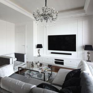 Biała szafka pod telewizor w lekko dekoracyjnymi frontami pięknie prezentuje się w połączeniu ze ścianą, którą zdobią sztukaterię. Projekt: Katarzyna Mikulska-Sękalska. Fot. Bartosz Jarosz