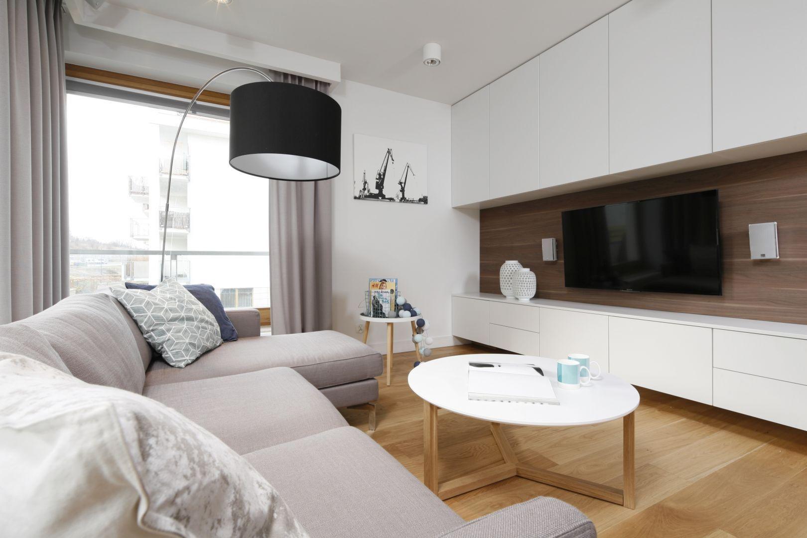 Szafka pod telewizor w salonie jest częścią białej zabudowy, która oferuje dużo miejsca na przechowywanie. Projekt: Przemysław Kuśmierek. Fot. Bartosz Jarosz