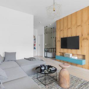 Szafka pod telewizor w salonie w turkusowym kolorze jest ładną dekoracją na tle drewnianego panelu dekoracyjnym. Projekt: Alina Fabirowska. Fot. Pion Poziom