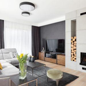 Drewniana szafka pod telewizor ładnie pasuje do ciemnego wykończenia ściany. Projekt: Katarzyna Maciejewska. Fot. Dekrialove