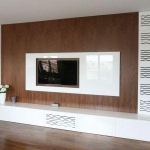Biała szafka pod telewizor w salonie z fontami w połysku pięknie wygląda w połączeniu z ciepłym drewnem. Projekt Agnieszka Ludwinowska. Fot. Bartosz Jarosz