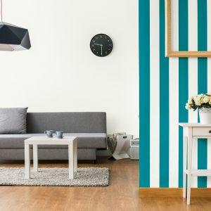 Kreatywnym sposobem na upiększenie salonu jest zastosowanie na fragmencie ściany pasów w świeżym połączeniu stonowanej bieli i urzekającego odcienia Magia turkusu z kolekcji Jedynka Deco & Protect Zmywalna. Fot. Jedynka