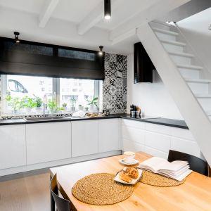 Biel w kuchni pięknie uzupełniają elementy w czarnym kolorze. Projekt i zdjęcia: Monika Staniec