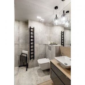 Nowoczesną łazienkę wykończono szarymi płytkami. Projekt i zdjęcia: Monika Staniec