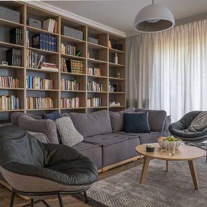 W przytulnym salonie świetnie prezentuje się duży regał na książki za kanapą. Projekt: Jacek Tryc. Fot. Jacek Tryc - wnętrza
