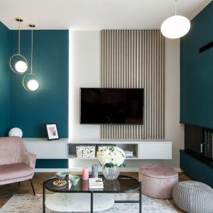 Ściana za telewizorem w salonie wykończona kolorową farbą i drewnianymi lamelami. Projekt i wykonanie: KODO Projekty i Realizacje Wnętrz