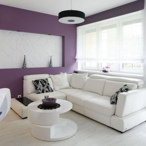 Ścianę w salonie wykończono w kolorze białym i fioletowym.  Projekt: Joanna Ochota. Fot. Bartosz Jarosz