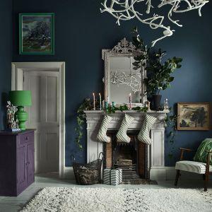 Ściana wykończona Chalk Paint w kolorze Aubusson Blue, kominek i rama lustra w kolorze Paloma, skarpety na prezenty i obicie fotela w tkaninie w prążki Ticking in Graphite. Fot. Annie Sloan