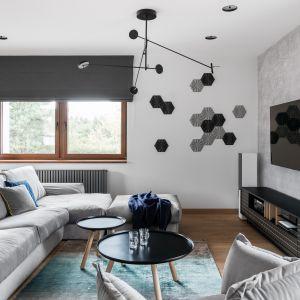 Telewizor powieszona na ścianie na przeciwko kanapy, co za pewni doskonałą widoczność. Ścianę zaś wyróżniono dekoracyjny stiukiem. Projekt Estera i Robert Sosnowscy. Fot. Fotomohito