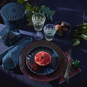 Kamionkowe miski z pokrywkami talerze w kolorze granatowym, wykonany z ceramiki porowatej fioletowy talerz oraz szklane kieliszki to propozycja aranżacji nowoczesnego stołu Vinter. Fot. IKEA