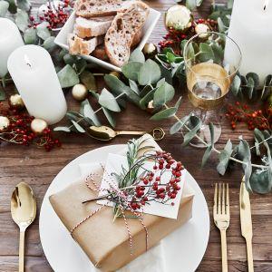 Aranżacja Tradycja to konwencjonalnie nakryty stół, który zdobi biała porcelana, złote dodatki oraz dekoracje świąteczne w kolorach kojarzonych z bożonarodzeniowymi tradycjami – czerwieni i zieleni. Fot. Westwing
