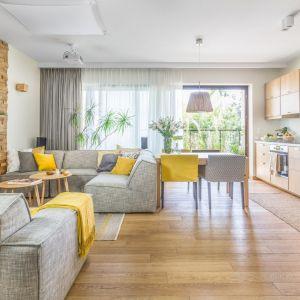 Przytulny salon urządzono w jasnych kolorach. Drewno pięknie łączy się z szarościami i kolorem żółtym. Projekt: Dorota Kudła-Kubrakiewicz. Fot. Pion Poziom