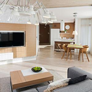 W przytulnym, jasnym salonie drewniana jest podłoga, panele telewizyjny oraz sufit. Projekt: Maciej Brzostek. Fot. Bartosz Jarosz