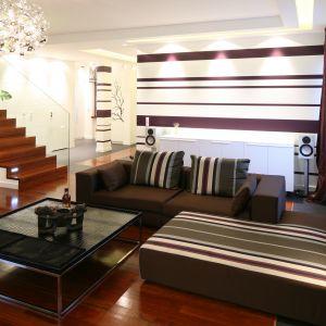 Ściana za kanapą w salonie została wykończona tapetą w biało-fioletowe ściany. Idealnie pasuje ona do poduszek i kanapy. Projekt: Katarzyna Mikulska-Sękalska. Fot. Bartosz Jarosz