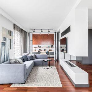 Białe ściany w salonie ociepla piękna, drewniana podłoga oraz jasny dywan. Projekt: Joanna Węgłowska, Wioletta Cieślik. Fot. Pion Poziom