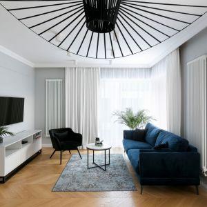 Do szarych ścian w salonie pięknie pasuje jasna, drewniana podłoga. Projekt: Paulina Zwolak, Jakub Nieć, pracownia Projektyw. Zdjęcia: Jakub Dziedzi