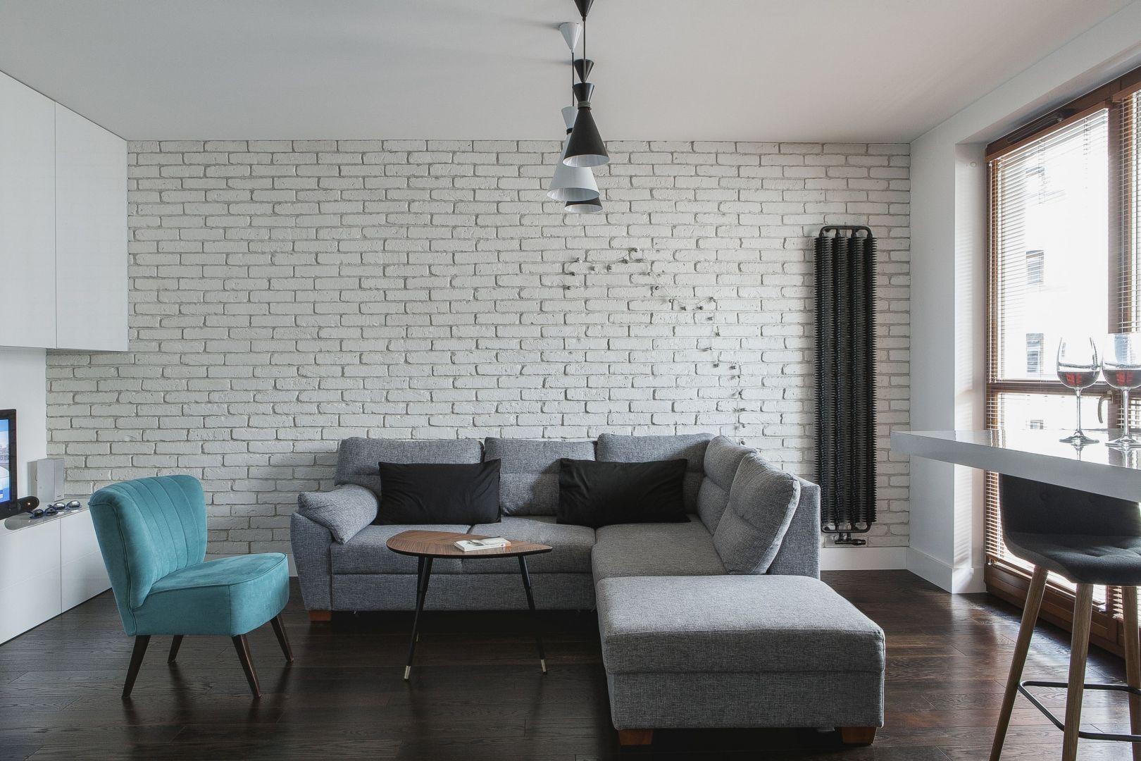 Biała cegła na ścianie idealnie pasuje do nowoczesnego salonu. Projekt i zdjęcia: MAFGROUP