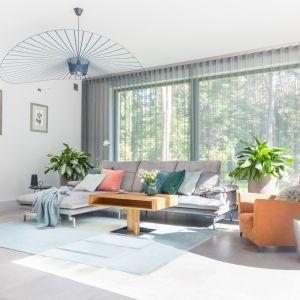 Aranżacja tego salonu oparta o biel i jasne szarości stała się idealnym tłem dla kolorowych dodatków. Projekt Małgorzata Dents. Fot. Pion Poziom