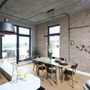 Styl loftowy opiera się na połączeniu naturalnych materiałów, takich jak drewno, z elementami metalowymi – zazwyczaj malowanymi proszkowo na czarny kolor. Projekt: Maciejka Peszyńska-Drews. Fot. Fot. Bartosz Jarosz