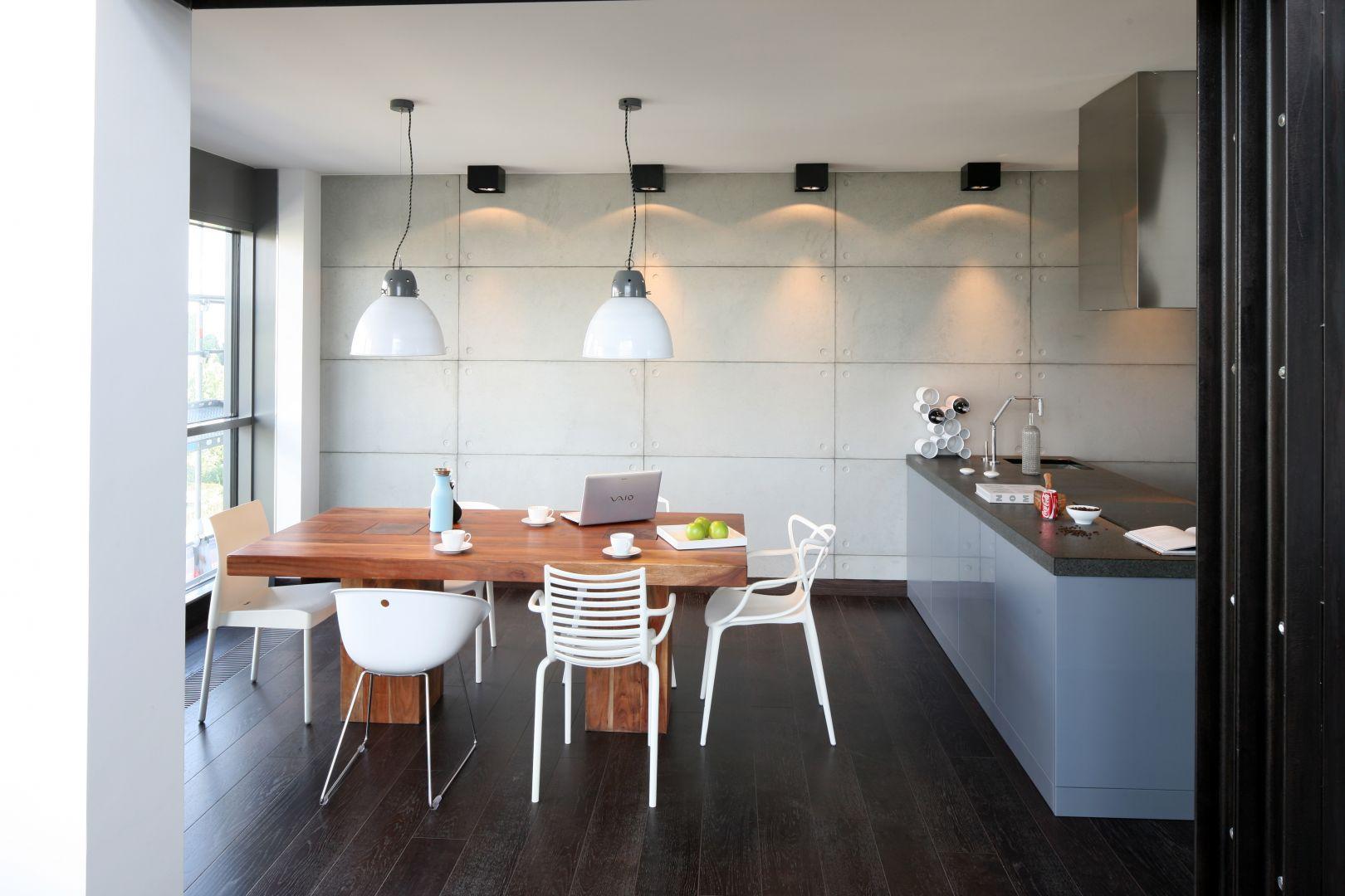 Beton na ścianie, masywny, drewniany stół i białe, lekkie krzesła to świetny wybór do jadalni w stylu loft. Projekt: Justyna Smolec. Fot. Bartosz Jarosz