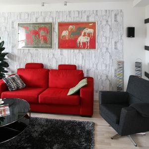 Czarny fotel w zestawie z czerwoną kanapą tworzy ciekawą, fajną strefę wypoczynku w salonie. Projekt: Marta Kruk. Fot. Bartosz Jarosz