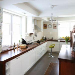 Ciemny, drewniany blat fajnie prezentuje się w jasnej kuchni. Projekt: Magdalena Misaczek. Fot. Bartosz Jarosz
