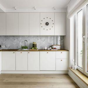 Kuchenny blat tworzy zgrany duet z drewnianą podłogą i białą zabudową meblową. Projekt: Saje Architekci. Fot. Fotomohito