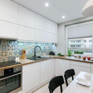 Białe meble w połysku i drewniany blat to idealnie połączenia nawet do małej kuchni w bloku. Projekt: Justyna Mojżyk. Fot. Monika Filipiuk-Obałek