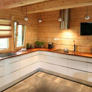 Drewniany blat i białe meble świetnie pasują do ściana z drewnianych bali. Projekt: Tomasz Motylewski, Marek Bernatowicz. Fot. Bartosz Jarosz