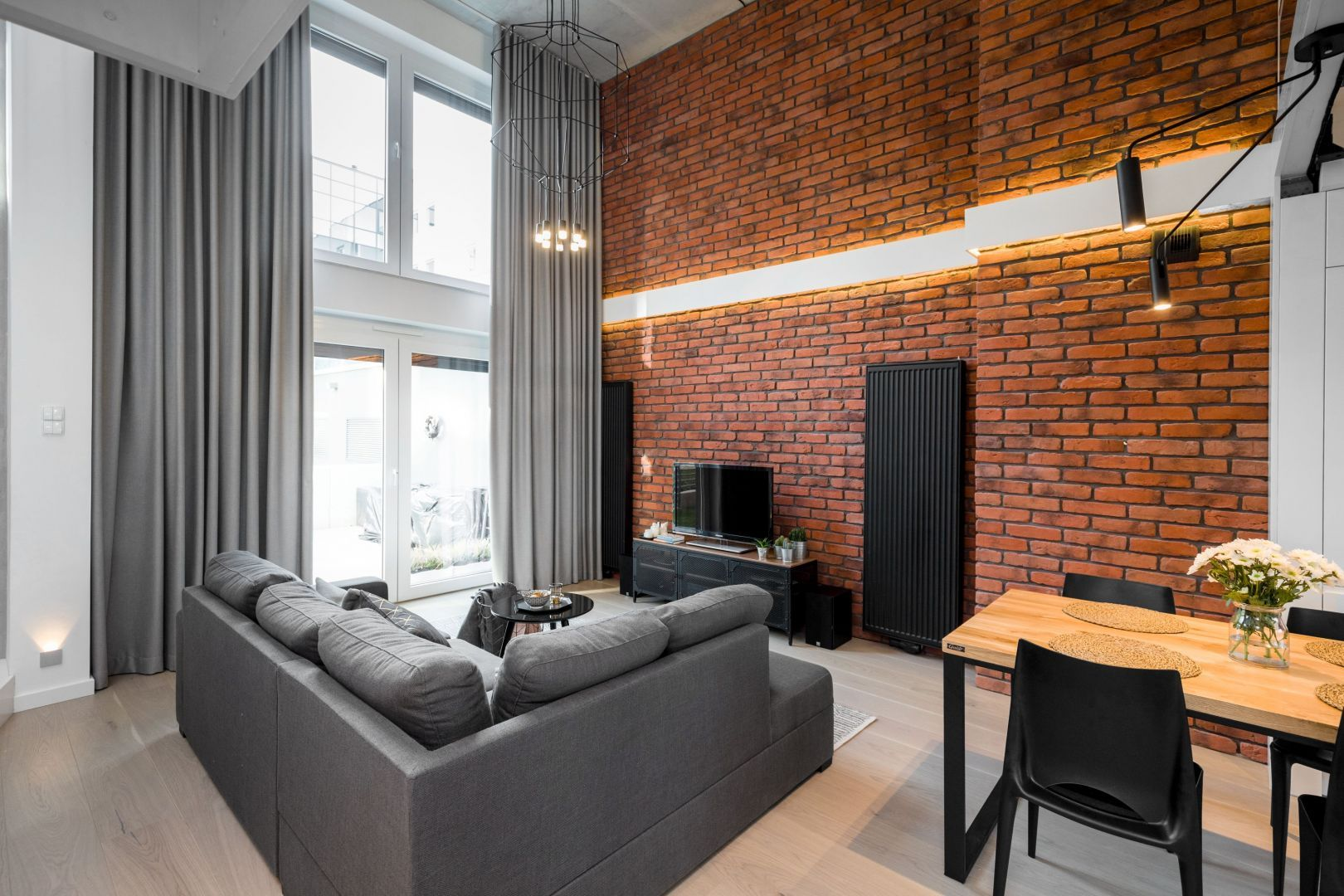 W nowoczesnym salonie szare zasłony stanowią piękną dekoracją dużego okna. Idealnie pasują do szarej sofy i czerwonej cegły na ścianie. Projekt i zdjęcia: Monika Staniec
