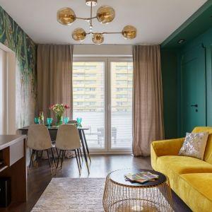 Zasłony w spokojnym beżowy kolorze doskonale pasuje do mocniejszego koloru ścian oraz kanapy w salonie. Projekt: Donata Gadalska. Fot. Jacek Fabiszewski