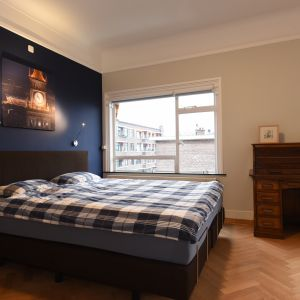 Sypialnia rodziców urządzona jest prosto, ale przytulnie. Klimatu dodaje jej ściana za łóżkiem w grantowym kolorze, na tle której pięknie prezentuje się fotografia Pałacu Kultury i Nauki w Warszawie. Projekt i zdjęcia: Marta Kruk, HeyHome
